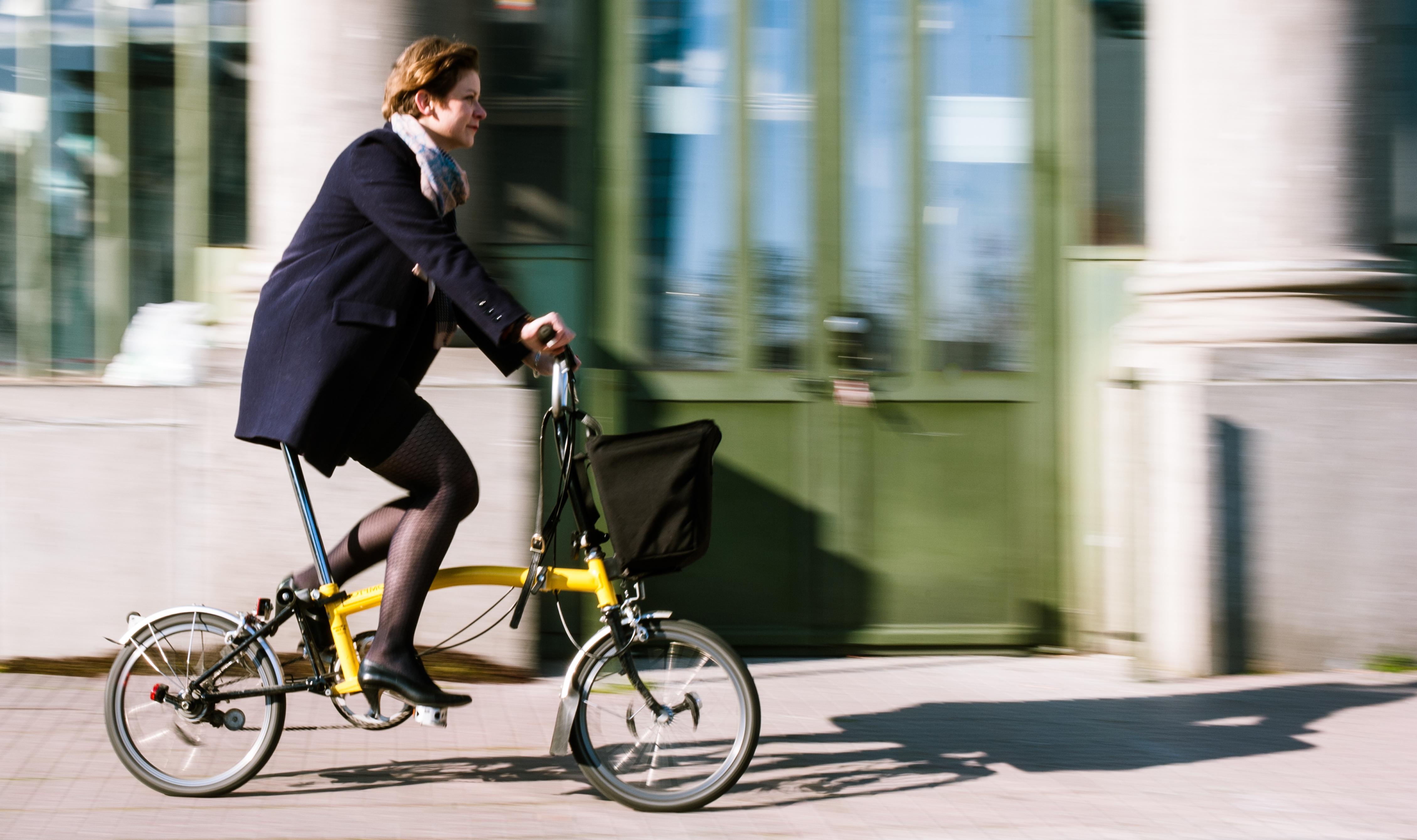 Vrouw fietsts met de plooifiets naar het werk